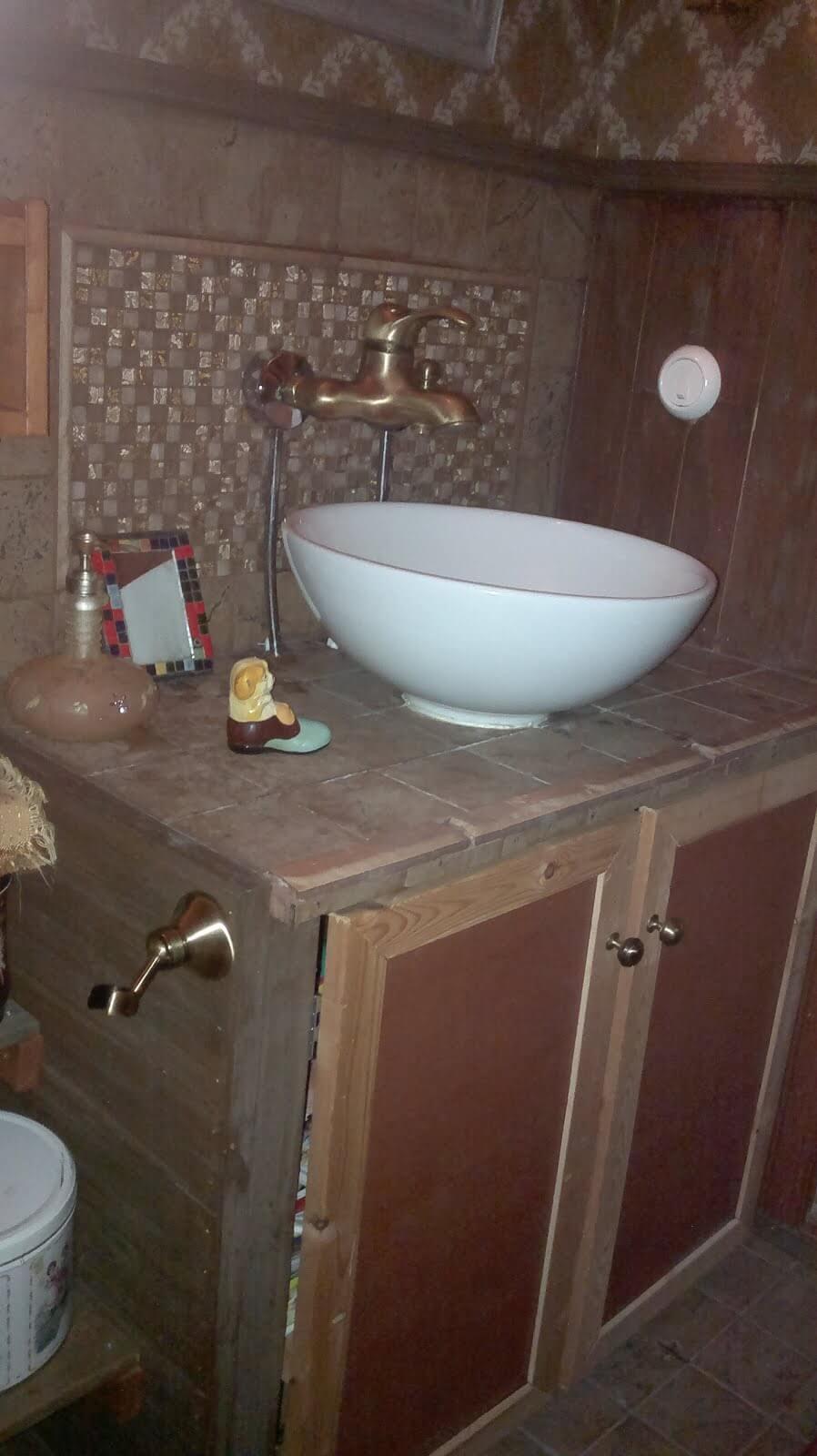 Yksityiskohtia vessaan laatoilla: kimaltavia mosaiikkilaattoja, rustiikkisia laattoja